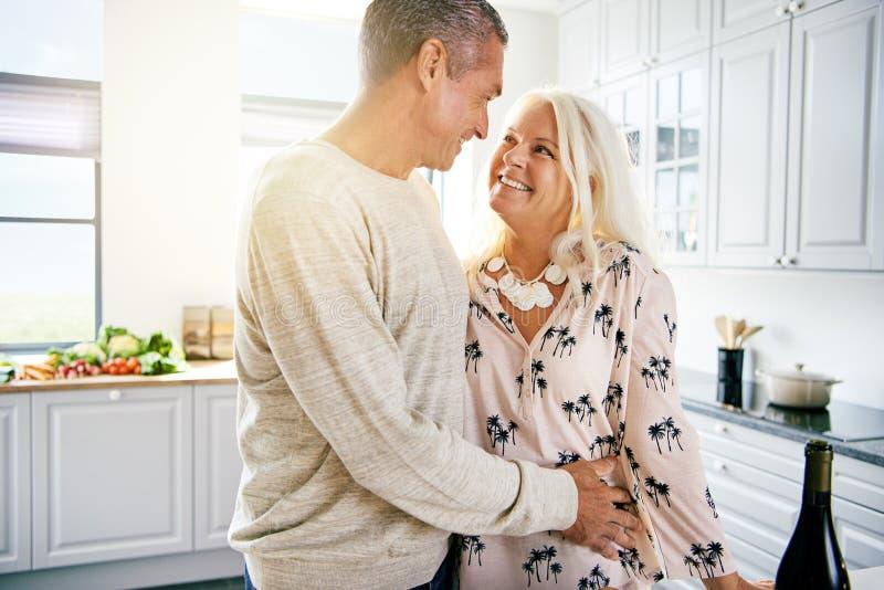 Hög manlig omfamna kvinna i kök royaltyfria bilder