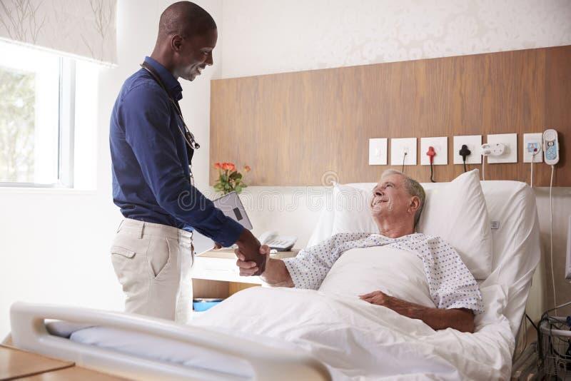 Hög manlig patient för doktor Shaking Hands With i sjukhussäng i geriatrisk enhet royaltyfri fotografi