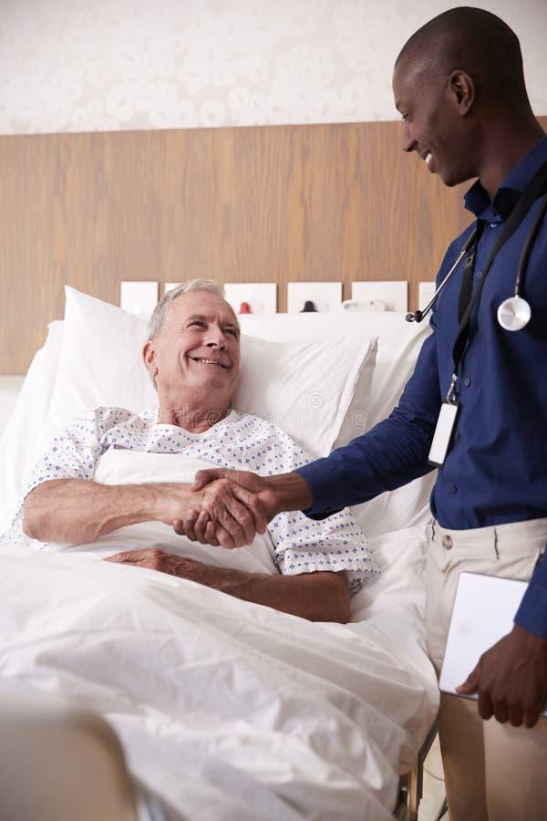 Hög manlig patient för doktor Shaking Hands With i sjukhussäng i geriatrisk enhet arkivfoto