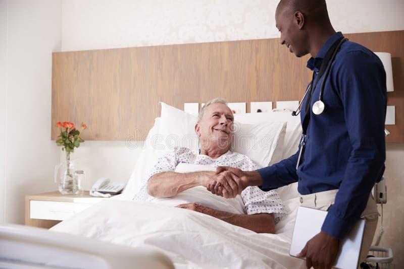 Hög manlig patient för doktor Shaking Hands With i sjukhussäng i geriatrisk enhet arkivbilder