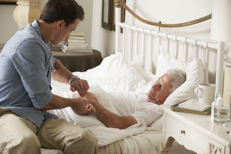 Hög manlig patient för doktor Taking Pulse Of i säng hemma royaltyfria foton