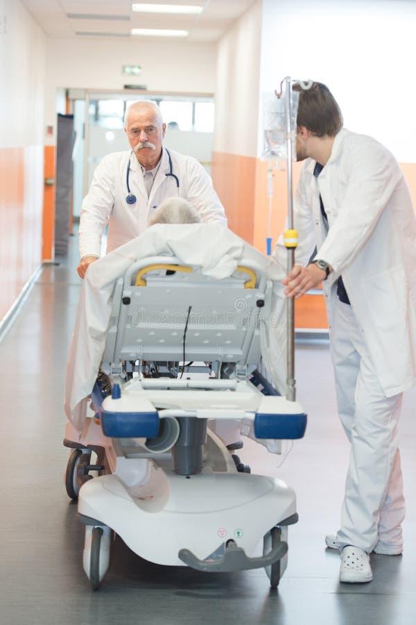 Hög manlig patient på båren som skjuts på hastighet fotografering för bildbyråer