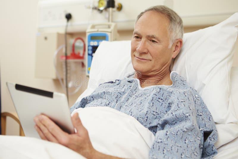 Hög manlig patient som använder den Digital minnestavlan i sjukhussäng arkivfoto