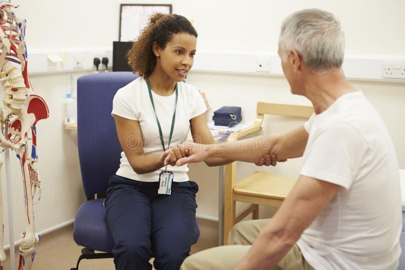 Hög manlig patient som har sjukgymnastik i sjukhus royaltyfria bilder