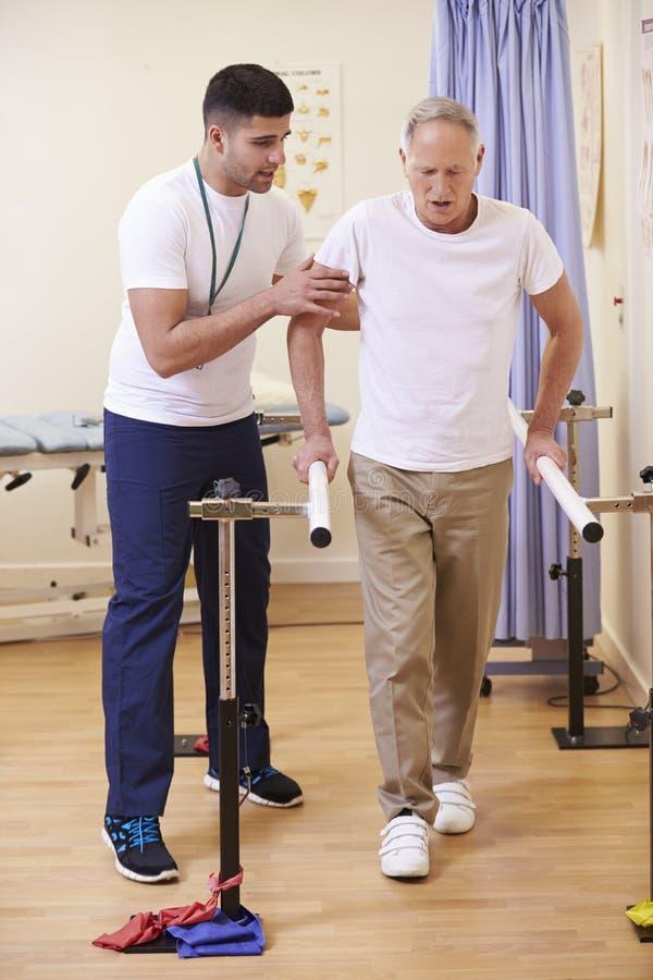 Hög manlig patient som har sjukgymnastik i sjukhus royaltyfri fotografi