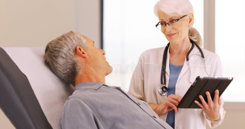Hög manlig patient som talar med doktorn om hans vård- bekymmer arkivfoto