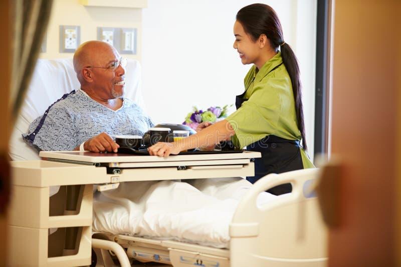 Hög manlig patient som tjänas som mål i sjukhussäng arkivfoto