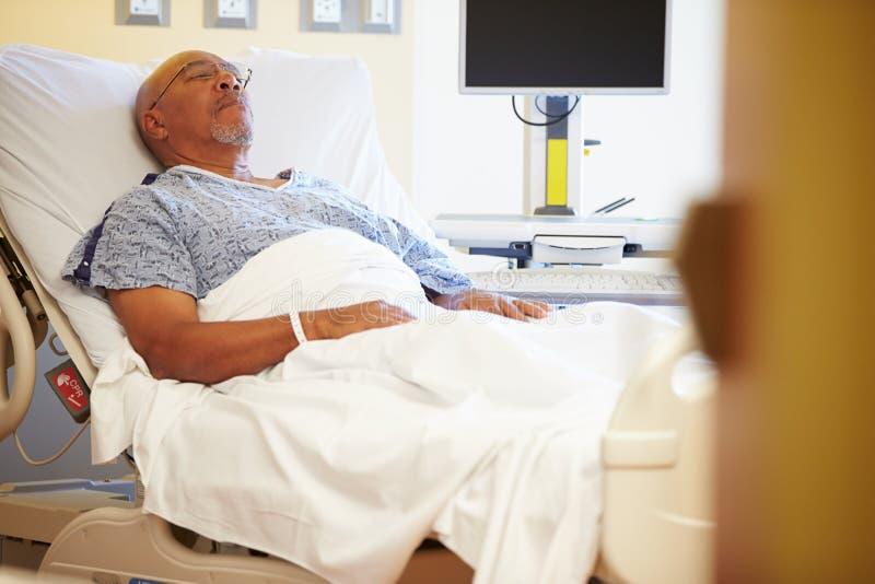 Hög manlig patient som vilar i sjukhussäng royaltyfri bild