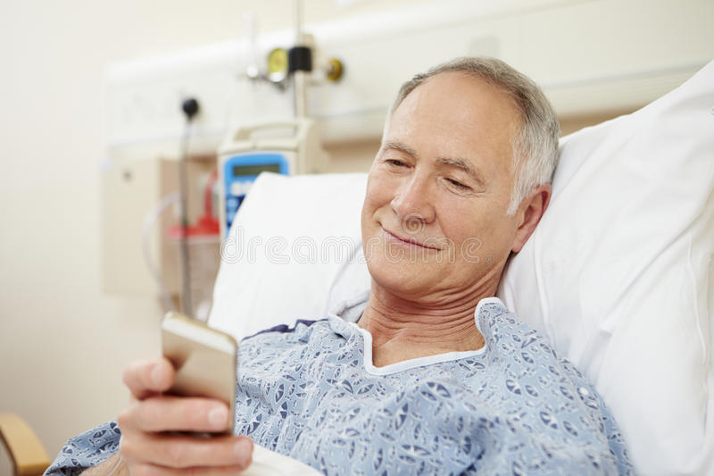 Hög manlig tålmodig användande mobiltelefon i sjukhussäng royaltyfri foto