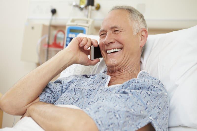 Hög manlig tålmodig användande mobiltelefon i sjukhussäng royaltyfri bild