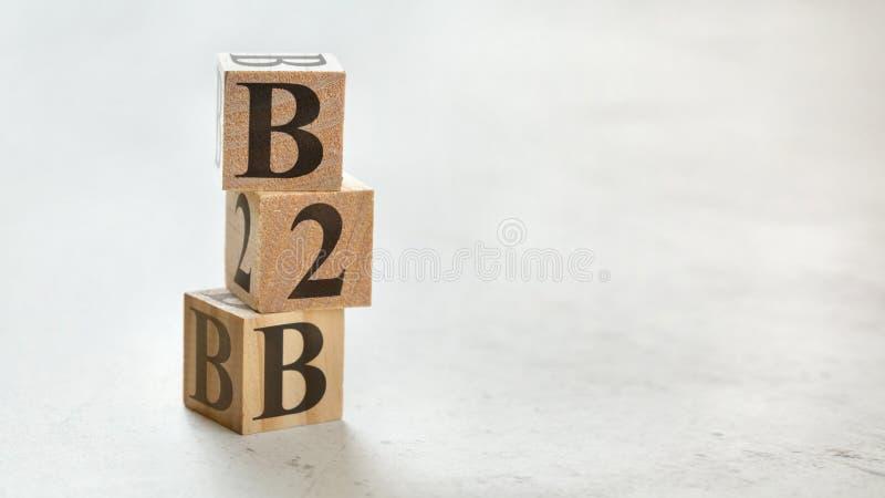 Hög med tre träkuber - affär för bokstavsB2B betydelse till affären på dem, utrymme för mer text/bilder på rätsidan arkivbild