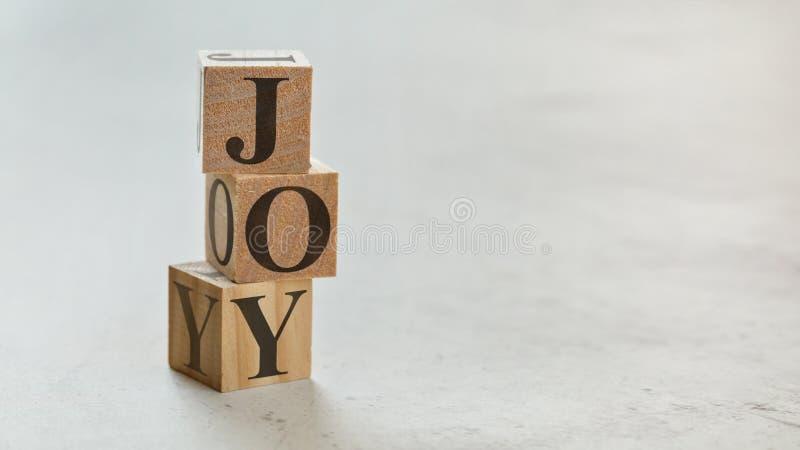 Hög med tre träkuber - bokstavsGLÄDJE på dem, utrymme för mer text/bilder på rätsida royaltyfria foton