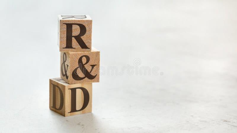 Hög med tre träkuber - bokstavsR&D som betyder forskning och utveckling på dem, utrymme för mer text/bilder på rätsidan royaltyfri fotografi