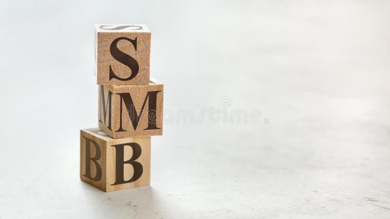 Hög med tre träkuber - bokstavsSMB betydelse som är liten till den medelstora affären på dem, utrymme för mer text/bilder på rätt arkivfoton