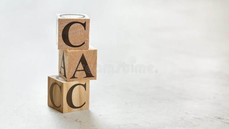 Hög med tre träkuber - för betydelsekund för bokstäver CAC kostnad för förvärv på dem, utrymme för mer text/bilder på rätsidan arkivbilder