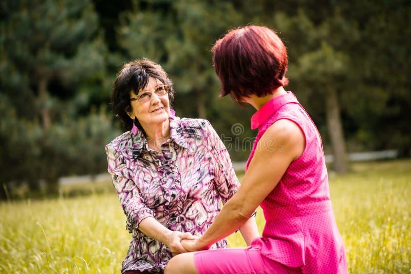 Hög moder och dotter som utomhus talar royaltyfri bild