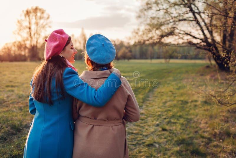 Hög moder och hennes vuxen dotter som går i vårskogmoders begrepp för dag Familjev?rderingar arkivfoto