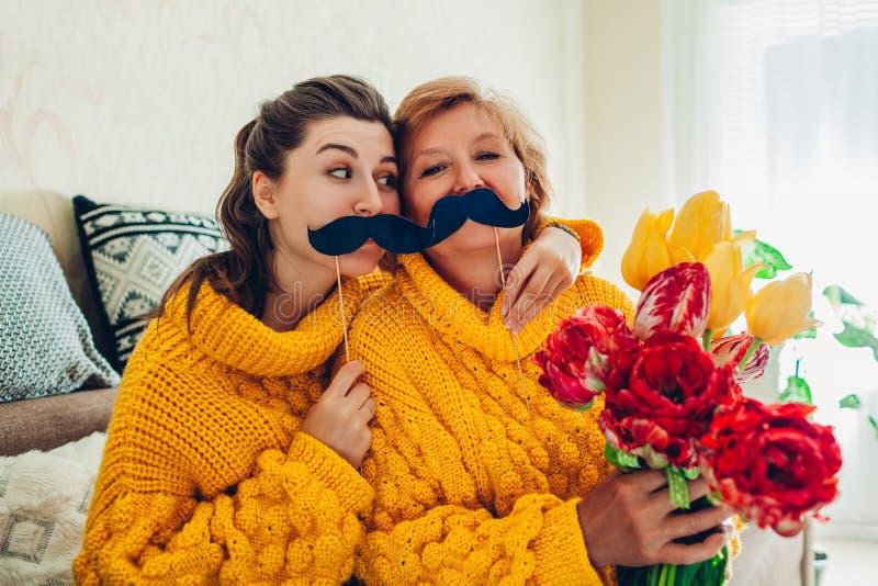 Hög moder och hennes vuxen dotter som tar selfie med blommor genom att använda fotobåsstöttor hemma Fostra dagbegreppet f?r ` s arkivfoto