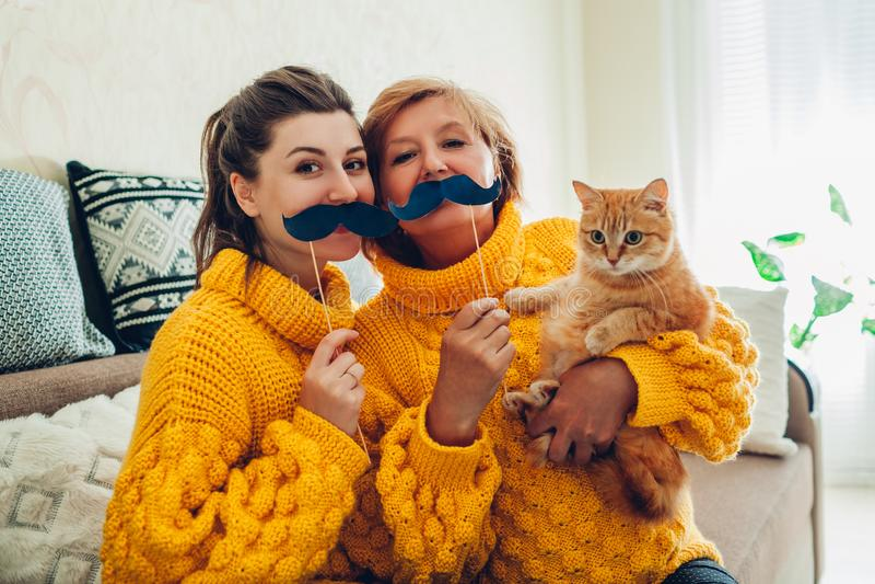 Hög moder och hennes vuxen dotter som tar selfie med katten genom att använda fotobåsstöttor hemma Fostra dagbegreppet f?r ` s royaltyfri fotografi