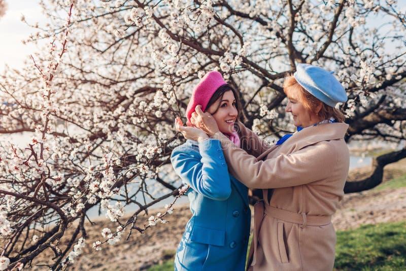 Hög moder som kontrollerar basker av hennes vuxna dotter, i att blomma trädgården Fostra dagbegreppet f?r ` s Familjev?rderingar royaltyfri fotografi