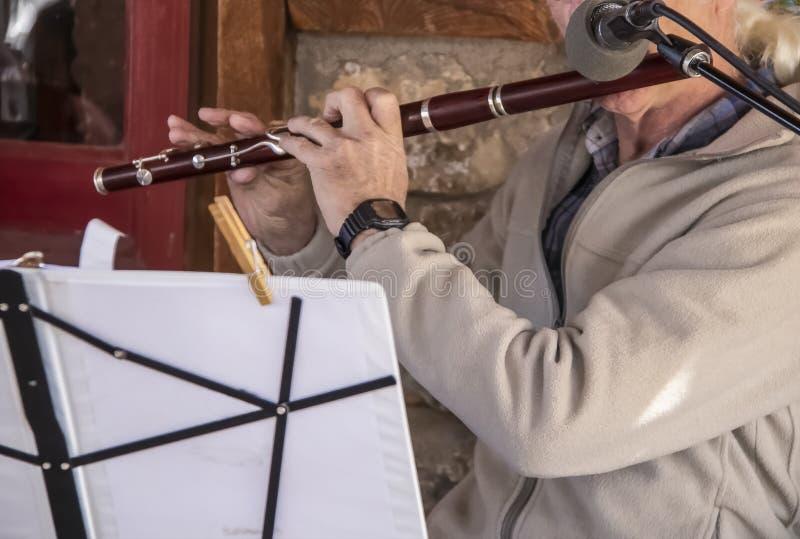 Hög musiker - äldre man spelar en flöjt - closeup med musik på ställning och mikrofonen royaltyfria foton