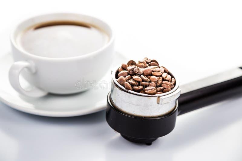 Hög nyckel- belysning av en kaffeportafilter fyllde med kaffebönor med en kopp av nytt bryggad espresso på bakgrunden royaltyfria bilder