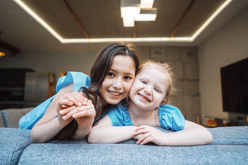 Hög och mer ung dotter på den stora soffan royaltyfria bilder