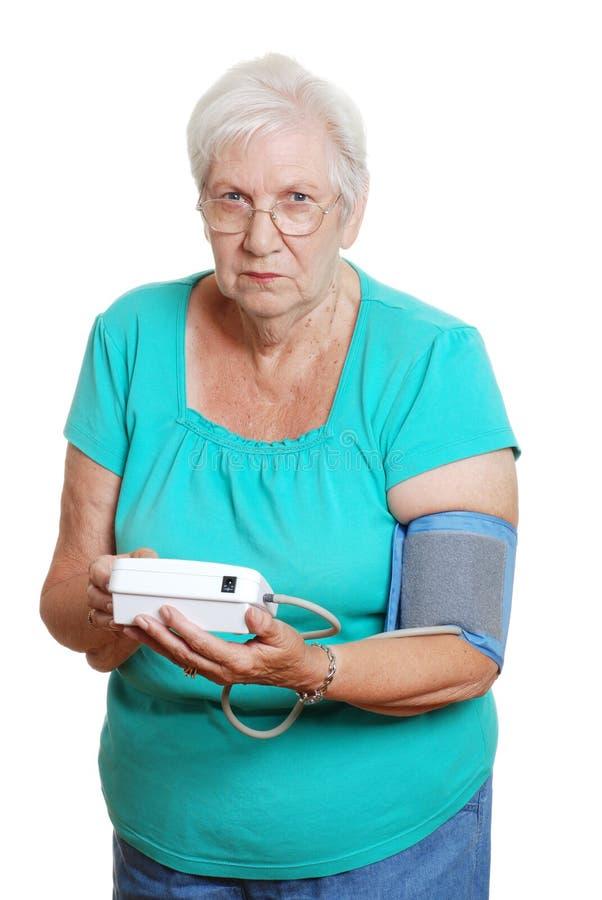 hög olycklig användande kvinna för automatisk blodpressur arkivbild