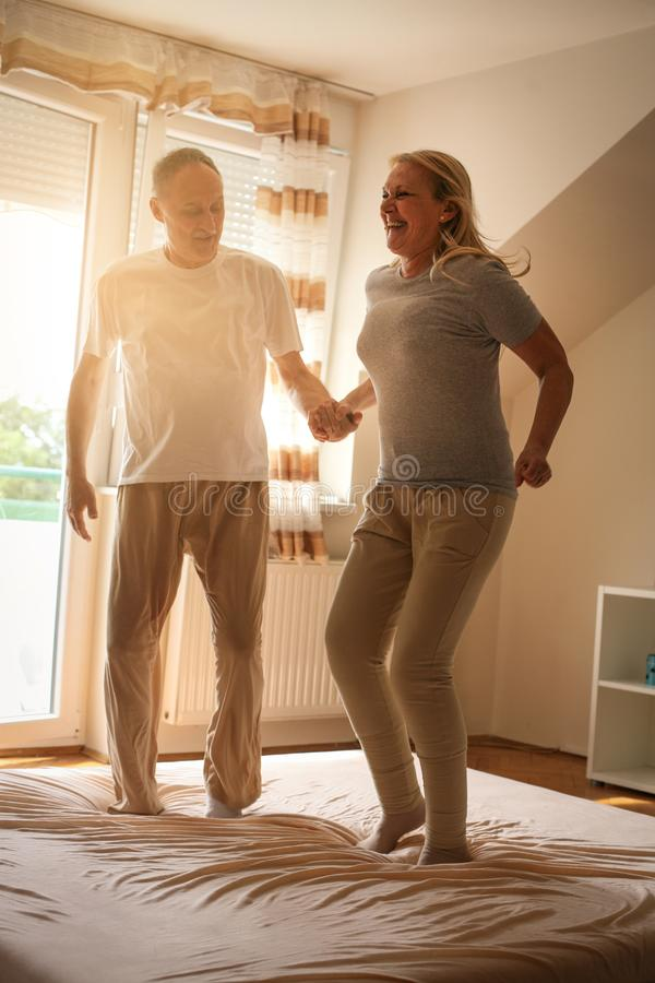 Hög pardans och banhoppning tillsammans på sänginnehavhänder fotografering för bildbyråer