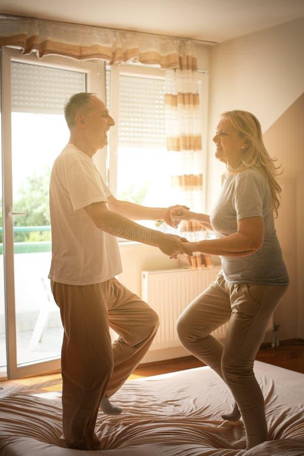 Hög pardans och banhoppning tillsammans på sänginnehavhänder arkivbilder