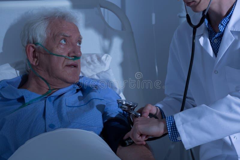 Hög patient som undersöks av doktorn royaltyfri fotografi