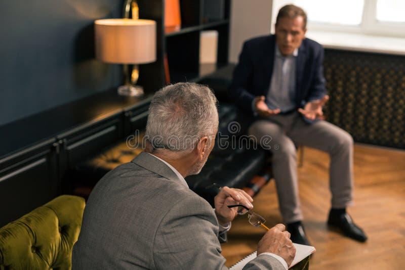 Hög psykoterapeut som framme sitter av hans patient royaltyfri bild