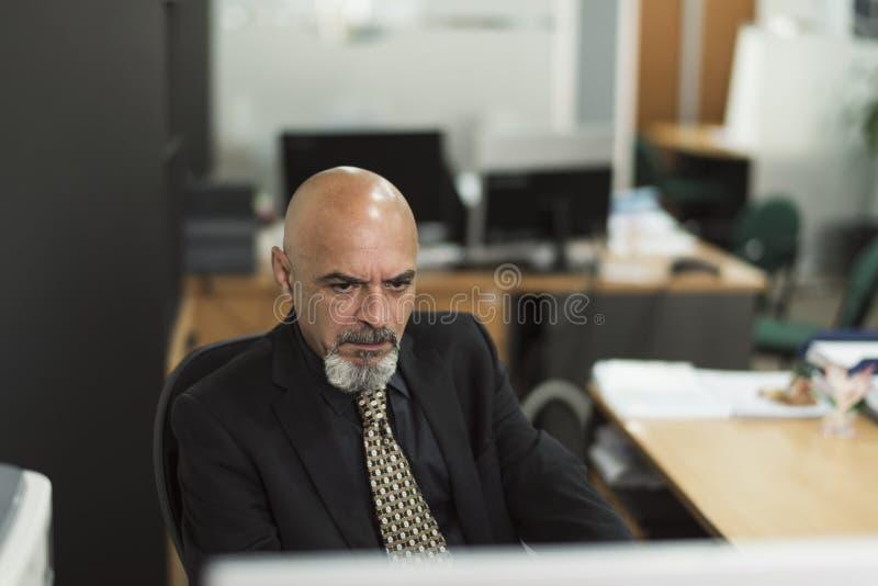Hög skallig man som i regeringsställning arbetar med den svarta dräkten arkivfoto