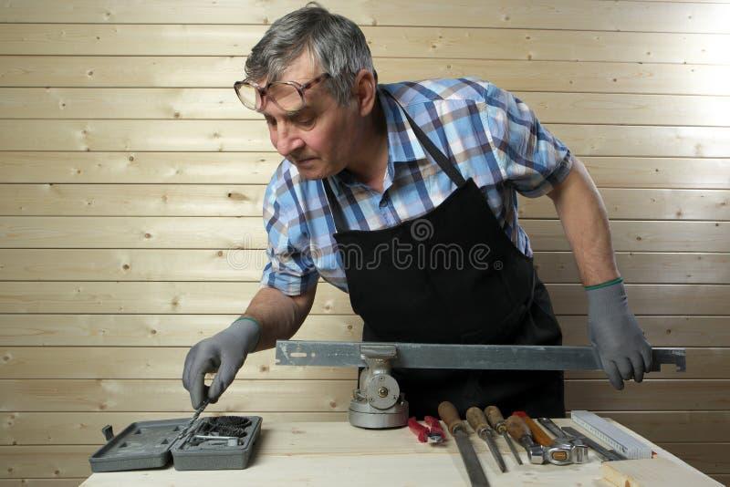 Hög snickare som arbetar i hans seminarium arkivfoto