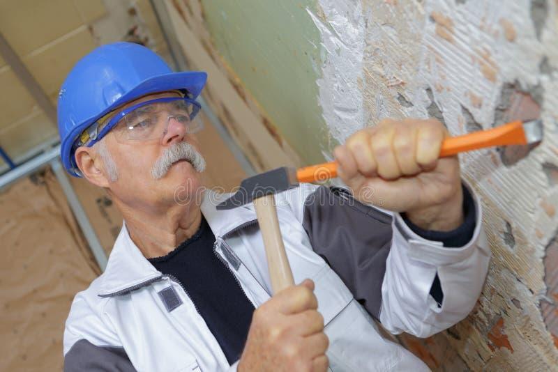 Hög snickare som arbetar med hammaren och stämjärnet arkivfoto
