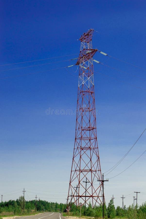 Hög-spänning elektrisk hög-spänning pylon mot en blå himmel Framdel- och bottensikt arkivfoton