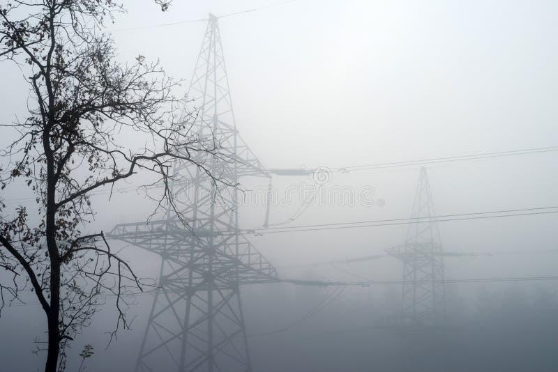 Hög-spänning elektriskt torn i dimman mot bakgrunden av skogen royaltyfri fotografi
