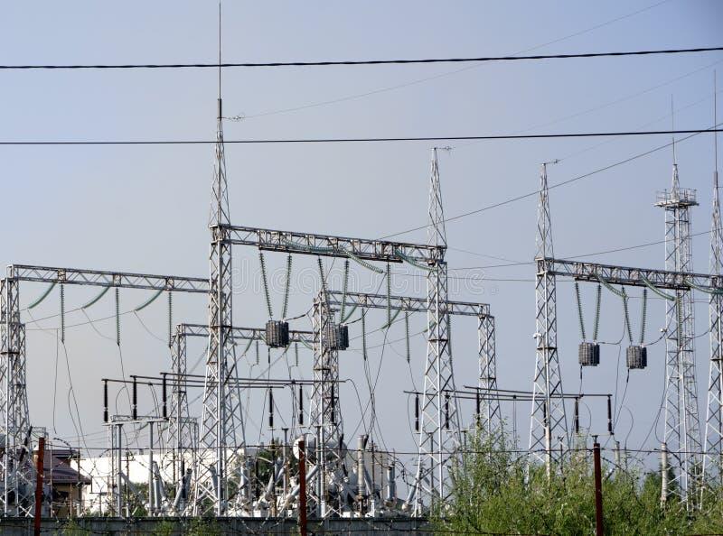Hög-spänning fodrar mot bakgrunden av stationer för elektrisk fördelning på soluppgång arkivbild