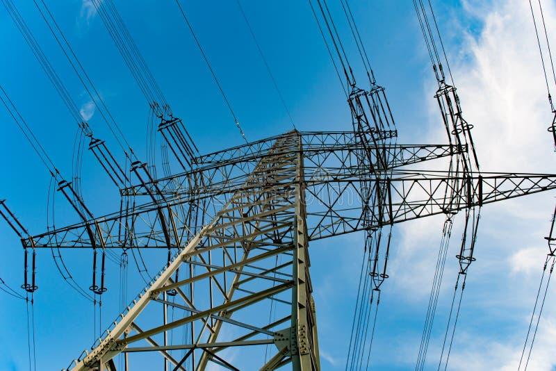 Hög-spänning kraftledning i blå himmel med moln Överföringslinjer, elektricitetspylon arkivfoton