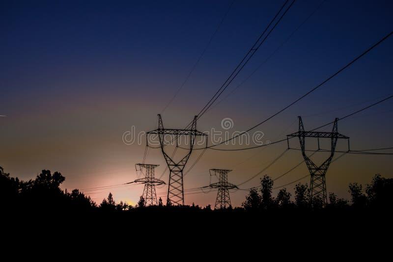 Hög-spänning kraftledningar på solnedgången elektricitetsfördelningssta fotografering för bildbyråer