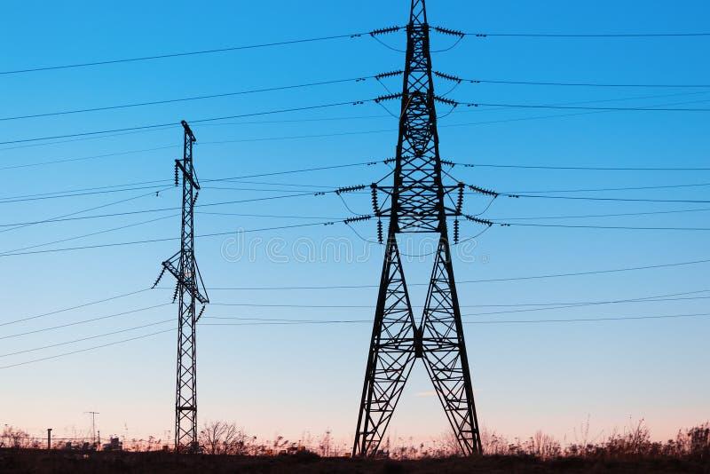 Hög-spänning kraftledningar på solnedgången Elektricitetsfördelningsstation arkivfoto