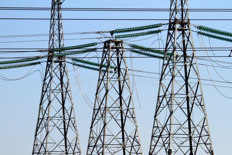 Hög-spänning kraftledningar på solnedgången Elektricitetsfördelningsstation Elektriskt överföringstorn för hög spänning arkivfoton