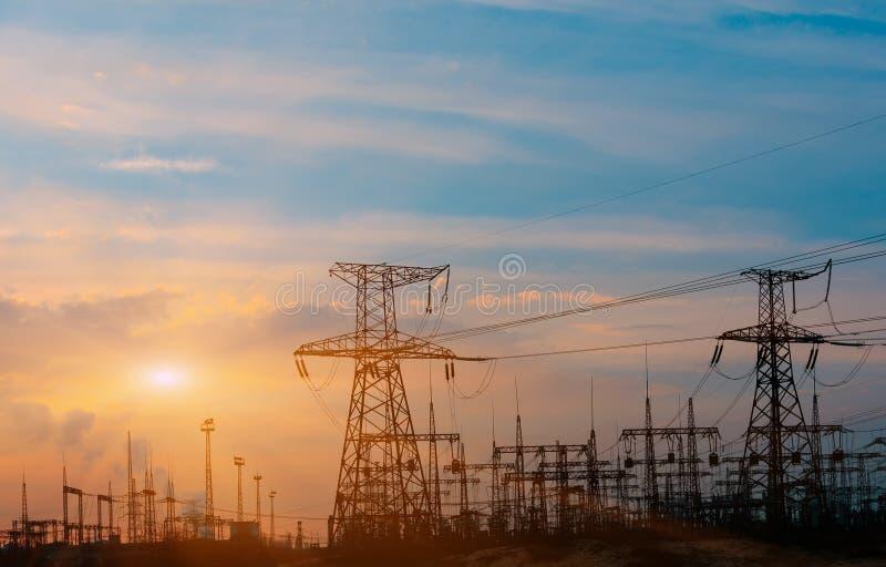 Hög-spänning kraftledningar på solnedgången Elektricitetsfördelningsstation Elektriskt överföringstorn för hög spänning arkivfoto