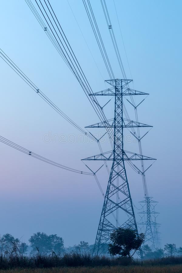 Hög-spänning maktpoler med bygden tidigt på morgonen royaltyfri foto