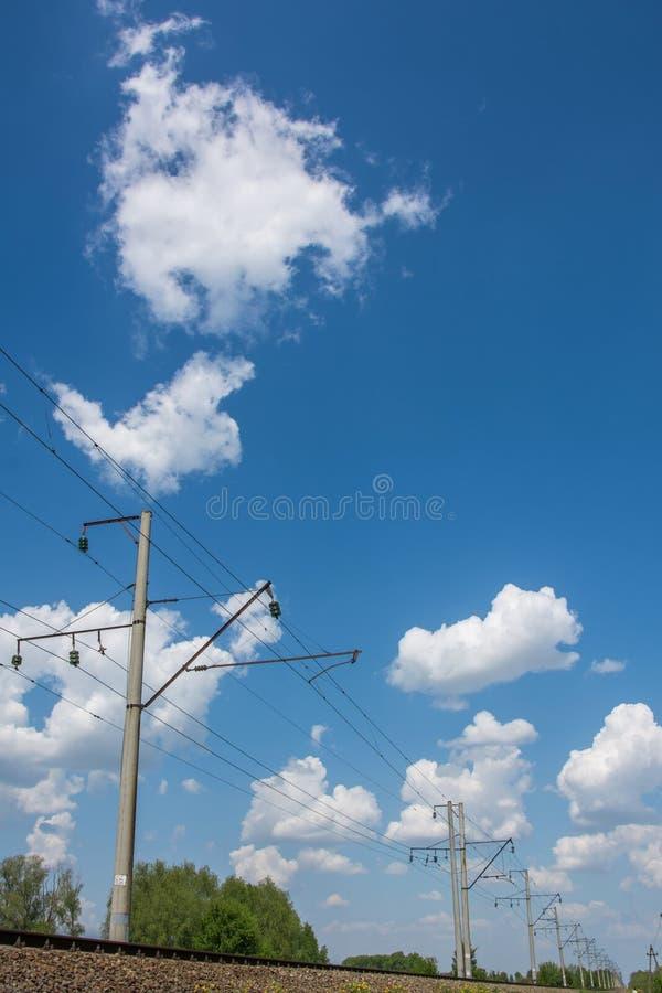Hög-spänning tråd längs järnväg under blå himmel royaltyfri fotografi