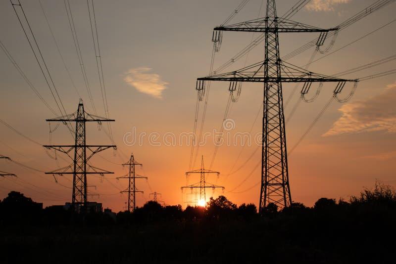 Hög spänningslinje, energi för folk, på solnedgången royaltyfri foto