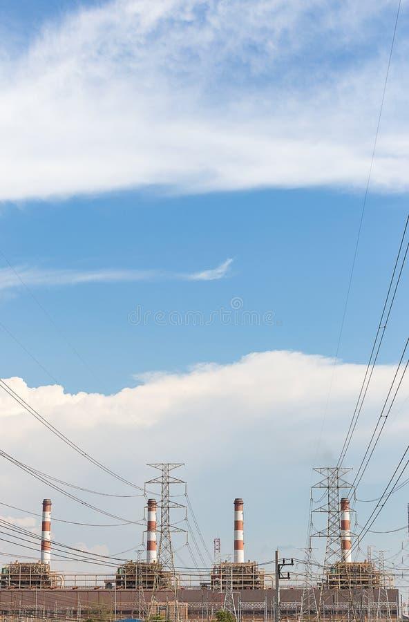 Hög spänningspol och elektricitetsväxt fotografering för bildbyråer