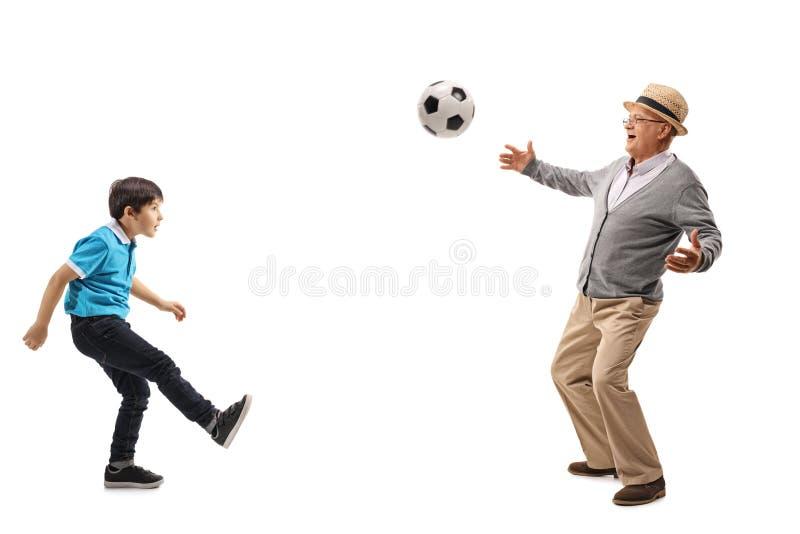 Hög spela fotboll med hans sonson royaltyfria foton