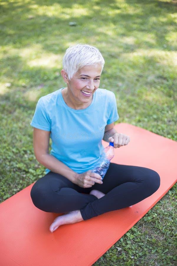Hög sportive kvinna som sitter på matt yttersida och vilar efter genomkörare arkivbild