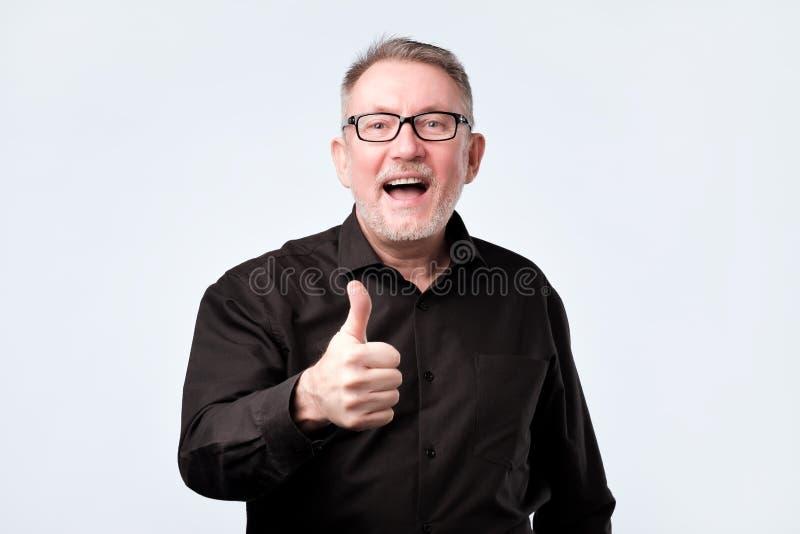 Hög stilig man i svart skjorta och exponeringsglas som visar tummar upp gest arkivfoto